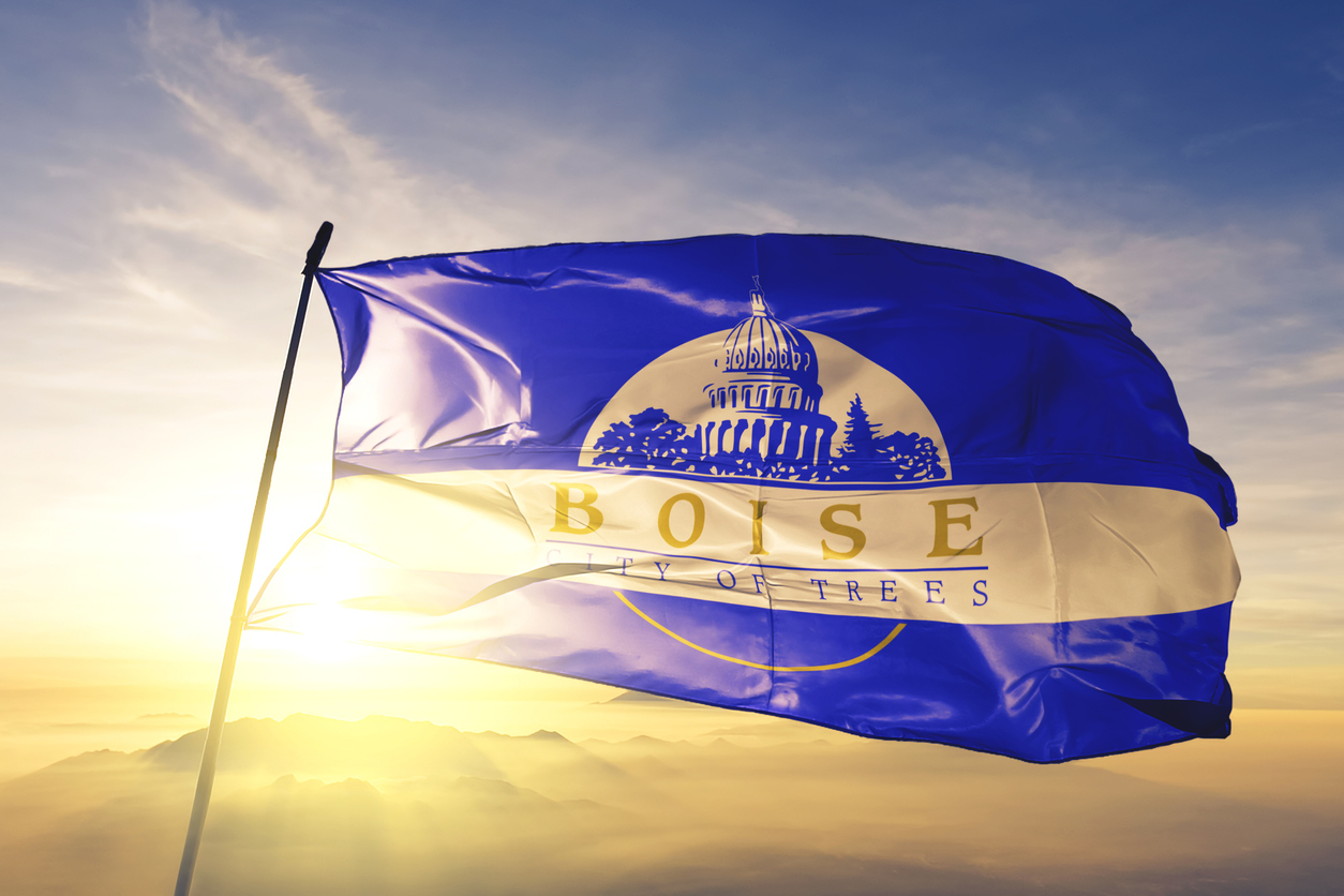 Boise city capital of Idaho of United States flag on flagpole textile cloth fabric waving on the top sunrise mist fog