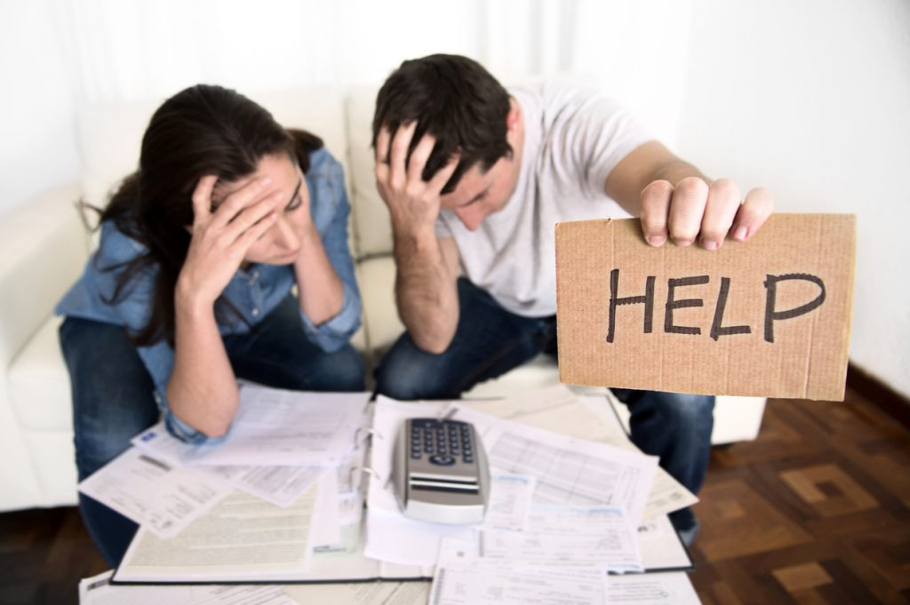 young couple worried in need of money asking for help in cardboard text message sitting in stress at home living room couch accounting debt bills bank , documents , receipts and payments feeling desperate in bad financial situation
