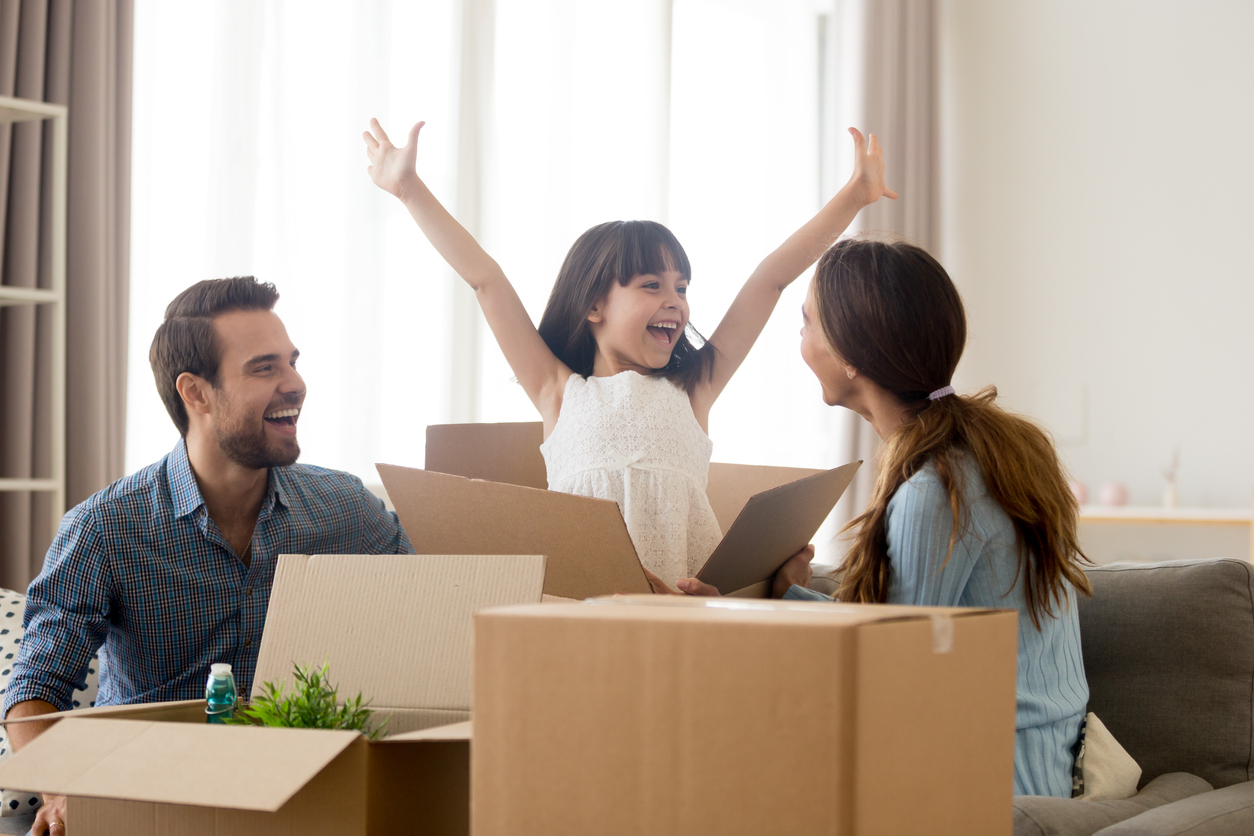 Happy kid daughter jumping out of box excited about moving day or relocation, cheerful child girl playing unpacking in new home with mom and dad, smiling family laughing having fun packing together